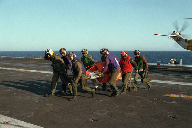 Crewmembers carry a litter across the flight deck of the aircraft carrier USS KITTY HAWK (CV 63) during a man overboard rescue drill
