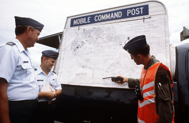Fifteen Air Base Wing officers, participating in a space shuttle emergency landing exercise, examine a map of the exercise area attached to the US Air Force Disaster Response Force mobile command post. They are, left to right: Colonel Fred Lugis, Lieutenant Colonel Willian H. Follmer, and COL Ronold J. Tribo, on-the-scene commander for the exercise