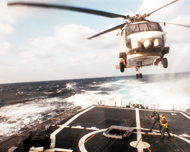 Two crewmen direct an SH-60B Seahawk helicopter preparing to land aboard the guided missile frigate USS MCINERNY (FFG-8) during testing of the Light Airborne Multi-Purpose System, Mark III (LAMPS III). Both the helicopter and the ship are equipped with LAMPS III components