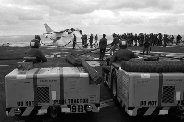 Two MD-3 tow tractors stand by as crewmen hose down an A7-E Corsair II aircraft during a fire drill aboard the aircraft carrier USS KITTY HAWK (CV 63)