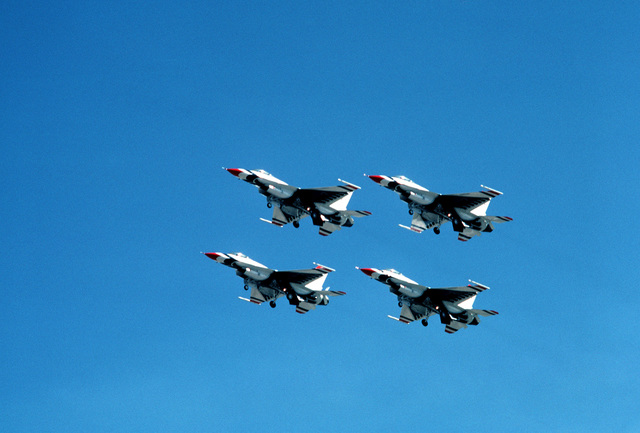 An air-to-air left front view of four F-16 Fighting Falcon aircraft flying in a diamond formation, as the Thunderbirds Flight Demonstration Team uses them for the first time in an air show