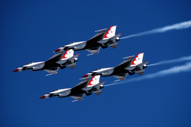 An air-to-air left side view of four USAF Thunderbird Air Demonstration Squadron F-16 Fighting Falcons in a diamond formation during their first air show