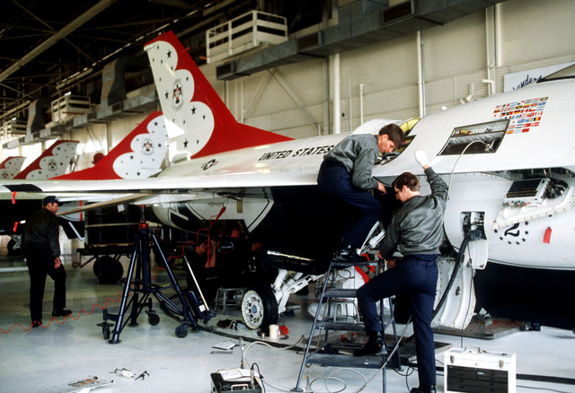 Maintenance personnel service one of the USAF Thunderbirds Air Demonstration Squadron's new F-16 Fighting Falcon aircraft prior to the team's first show