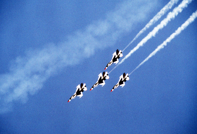 A ground-to-air view of four USAF Thunderbird F-16 Fighting Falcon aircraft performing an arrowhead loop. The Thunderbirds are making their first demonstration flight outside their home base at Nellis Air Force, Base, Nevada, since they were re-equipped with the F-16 aircraft
