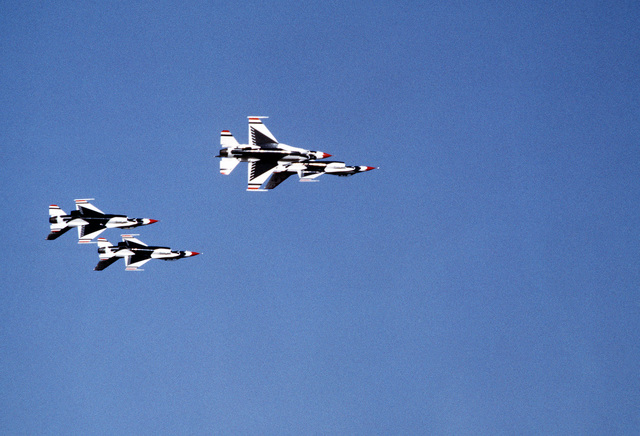A ground-to-air view of four USAF Thunderbird F-16 Fighting Falcon aircraft executing an aerial maneuver. The Thunderbirds are making their first demonstration flight outside their home base at Nellis Air Force, Base, Nevada, since they were re-equipped with the F-16 aircraft