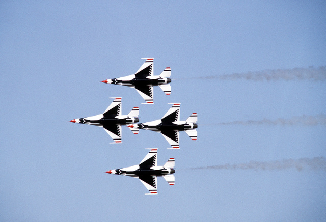 A ground-to-air view of four USAF Thunderbird F-16 Fighting Falcons in a diamond formation. The Thunderbirds are making their first demonstration flight outside their home base at Nellis Air Force, Base, Nevada, since they were re-equipped with the F-16 aircraft