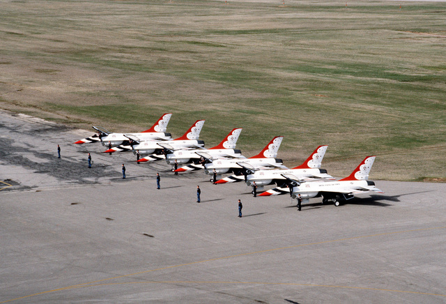 Six USAF Thunderbirds Aerial Demonstration Team pilots stand at attention in front of their F-16 Fighting Falcon aircraft during a preflight ceremony. The USAF Thunderbirds are making their first demonstration flight outside their home base at Nellis Air Force, Base, Nevada, since they were re-equipped with the F-16 aircraft