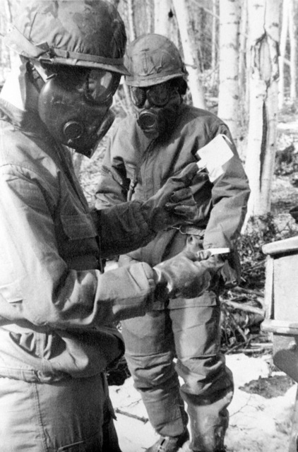 Members of the 1ST Battalion, 37th Field Artillery, use chemical test paper to find contamination levels near a jeep during NBC (Nuclear Biological Chemical warfare training