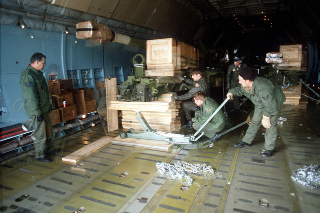 Air Force personnel put boards under the carriage of a 155mm M-198 howitzer with the help of a jack before securing it aboard a C-5 Galaxy aircraft. the gun is being transported to Thailand