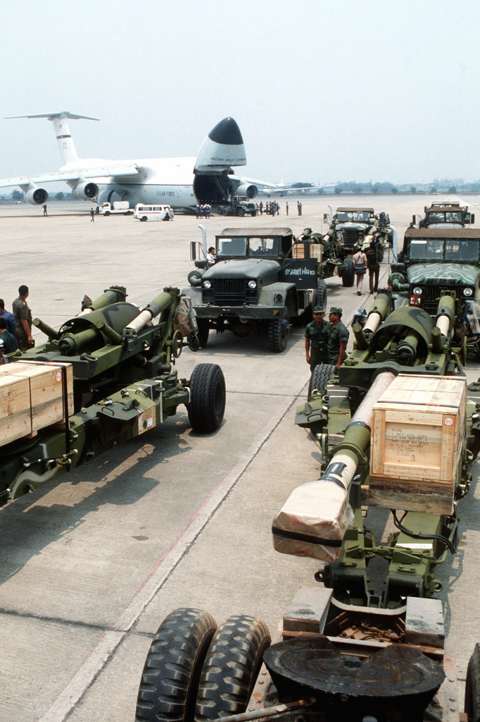M-198 155mm howitzers are staged on the flight line at Dong Muong International Airport after being off loaded from a C-5 Galaxy aircraft. The C-5 delivered eight M-198's to the Thai military