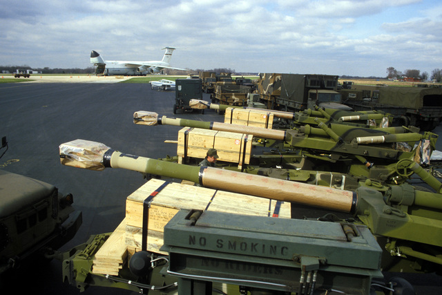 Three 155 mm M198 Howitzers to be loaded aboard a waiting C-5 Galaxy aircraft, background, for shipment to Thailand