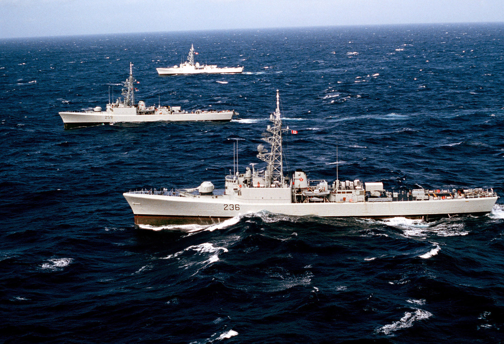 A port beam view of the Canadian frigates RESTIGOUCHE (257), rear, the TERRA NOVA (259), center, and the GATINEAU (236), front, underway during CINCPAC Exercise FLEETEX '83. The US Navy, Air Force, Coast Guard and the Canadian navy are participating in the exercise near the Aleutian Islands of Alaska
