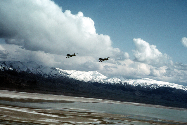 A left rear view of two A-6E Intruder aircraft from Carrier Air Wing Six, in flight with snow covered mountains in the background