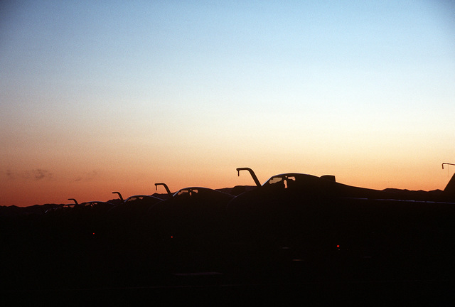 A silhouetted left front view of A-6E Intruder aircraft from Carrier Air Wing Six, parked on the flight line