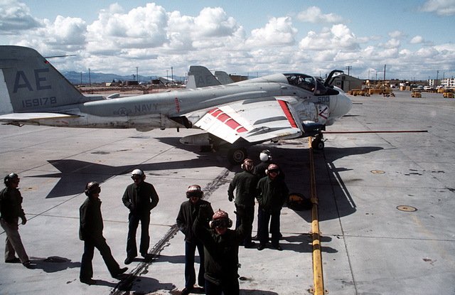 A view from the interior of an A-6E Intruder aircraft of a ground crewman directing it on to the flight line in preparation for bomb loading operations. The aircraft is assigned to Carrier Air Wing Six (CVW-6)