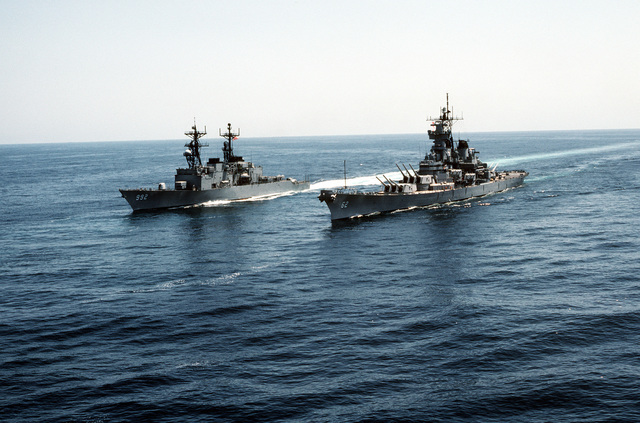 Aerial port bow view of the destroyer USS FLETCHER (DD-992) (left) and the battleship USS NEW JERSEY (BB-62). The ships are part of a task group underway off the coast of California