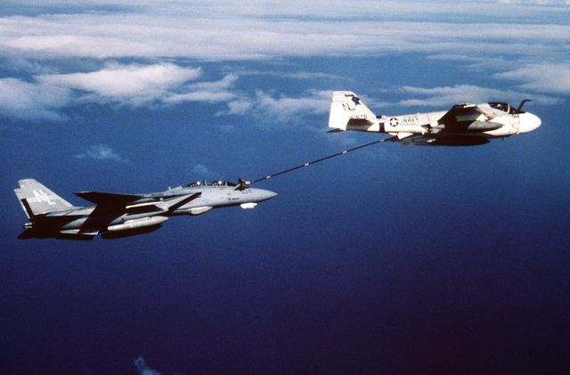 An air-to-air right side view of a KA-6D Intruder tanker aircraft from Medium Attack Squadron 52 (VA-52) refueling an F-14 Tomcat aircraft from Fighter Squadron 51 (VF 51). Both aircraft are assigned aboard the nuclear-powered aircraft carrier USS CARL VINSON (CVN 70)