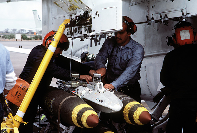 Ground crewman load bombs onto the pylon of an A-6E Intruder aircraft from Carrier Air Wing 6 (CVW-6)