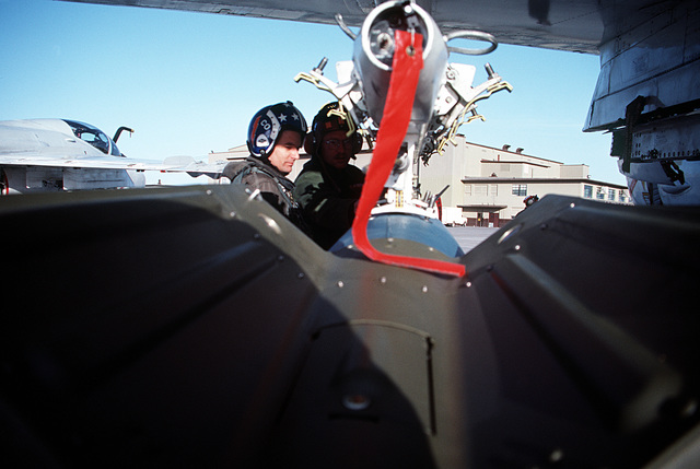 Ground crewman prepare to load a bomb onto the pylon of an A-6E Intruder aircraft from Carrier Air Wing Six (CVW-6)