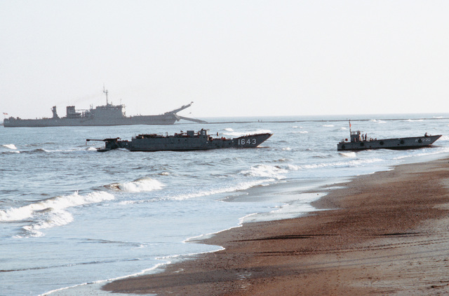 A Mark 8 mechanized landing craft (LCM), right, and the utility landing craft LCU 1643 come ashore during Exercise SOLID SHIELD '83. In the background is the Newport class tank landing ship USS MANITOWOC (LST 1180)