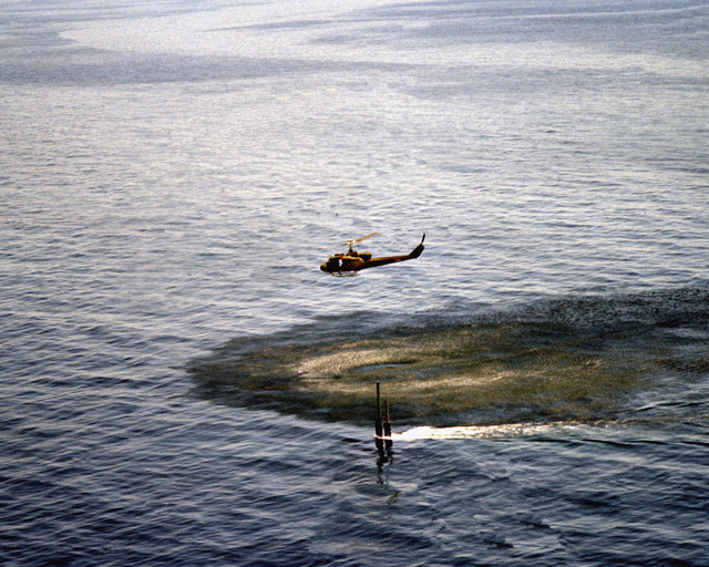 A UH-1 Iroquois helicopter flies over the nuclear-powered attack submarine USS LA JOLLA (SSN 701) during Tomahawk cruise missile tests on the Pacific Missile Test Center (PMTC) range