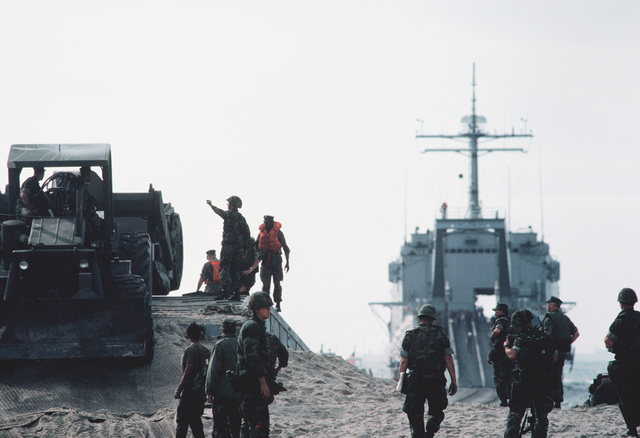 Heavy equipment is brought ashore from the Newport class tank landing ship USS MANITOWOC (LST 1180) during Exercise SOLID SHIELD '83