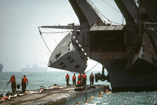 Preparations are made to lower the bow ramp of the Newport class tank landing ship USS MANITOWOC (LST 1180) during Exercise SOLID SHIELD '83