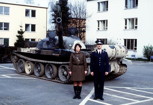 SSGT Loretta Martin, left, wearing a Soviet warrant officer's uniform, and SRA Dayne Padgett, wearing a Soviet special forces captain's uniform, stand in front of a Soviet T-62 battle tank at the Warrior Preparation Center