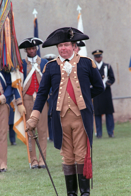 An officer dressed in the ceremonial uniform of the 1ST Maryland Regiment, Corps of the Continental Line, participates in the Cessation of Hostilities Bicentennial Celebration at the Pentagon River Plaza. Members of the 3rd United States Infantry (The Old Guard) are in the background. The Commemoration honors the issuance of a Continental Congress proclamation to the assembled Main Army at Newburgh, New York, that announced a cease-fire between Americans and the British forces of King George III