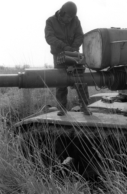 STAFF Sergeant Steve Colson, an M-60 tank commander with the 3/37th Armor, adjusts a Hoffman tank gunfire simulator during a training exercise. The barrel-mounted device simulates the firing of the tank's main gun