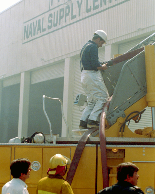 A firefighter prepares to climb a ladder during efforts to extinguish a fire that started in a Naval Supply Center building at Pier 4 of the Naval Station, and eventually spread to the converted Raleigh Class command ship USS LA SALLE (AGF-3)