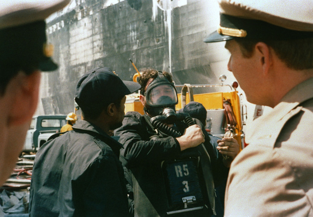 A firefighter wears an oxygen mask during efforts to extinguish a fire that started in a Naval Supply Center building at Pier 4 of the naval station. The fire eventually spread to the converted Raleigh class command ship USS LA SALLE (AGF 3)