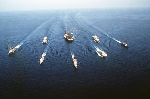An aerial bow view of the USS AMERICA (CV-66) Task Group during a fly-over of aircraft assigned aboard the aircraft carrier