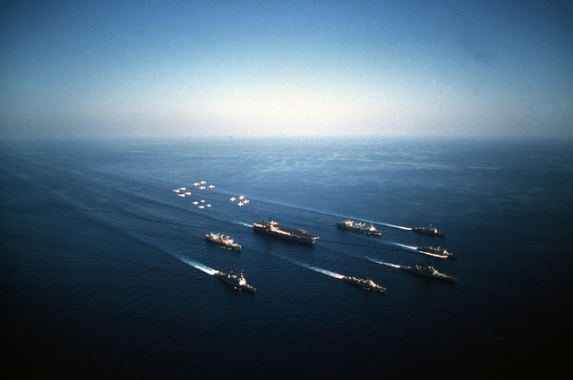 An aerial starboard view of the aircraft carrier USS AMERICA (CV 66) Task Group during a fly-over of aircraft assigned aboard the aircraft carrier