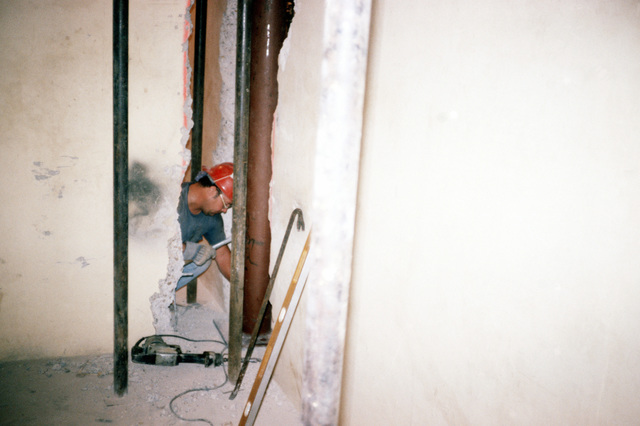 A workman begins the destruction of one of the many walls starting the destruction of the film storage vaults that must be demolished to make room for Defense Audiovisual Agency, which is consolidating the audiovisual functions of the four services and moving them together under one roof