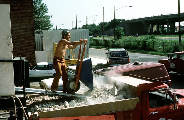 A workman empties the many wheelbarrows of dust and concrete created by the destruction of the film storage vaults that must be demolished to make room for Defense Audiovisual Agency, which is consolidating the audiovisual functions of the four services and moving them together under one roof