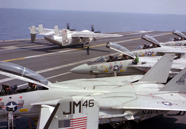 A C-2 Greyhound aircraft lands beside a row of F-14A Tomcat aircraft on the flight deck of the nuclear-powered aircraft carrier USS DWIGHT EISENHOWER (CVN-69)