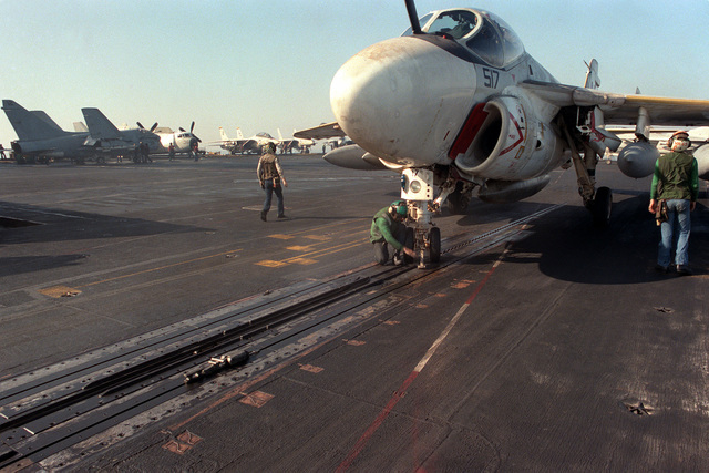 A catapult crewman reaches for the launch bar on the nose gear of an Attack Squadron 65 (VA-65) A-6E Intruder aircraft aboard the nuclear-powered aircraft carrier USS DWIGHT D. EISENHOWER (CVN 69)