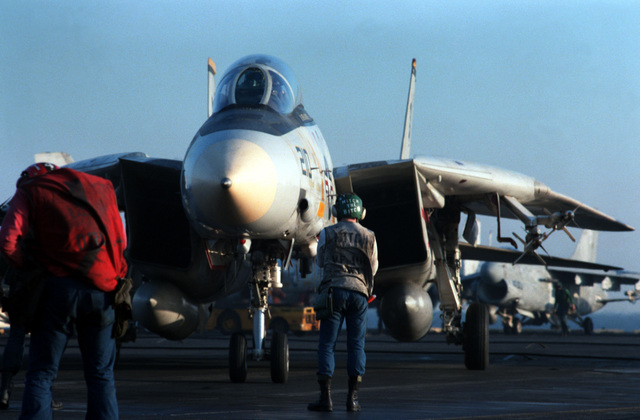 A Fighter Squadron 142 (VF-142) F-14A Tomcat aircraft is positioned on the flight deck of the nuclear-powered aircraft carrier USS DWIGHT D. EISENHOWER (CVN 69)