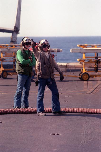 A flight deck crew member signals to a pilot during flight operations aboard nuclear-powered aircraft carrier USS DWIGHT D. EISENHOWER (CVN-69)
