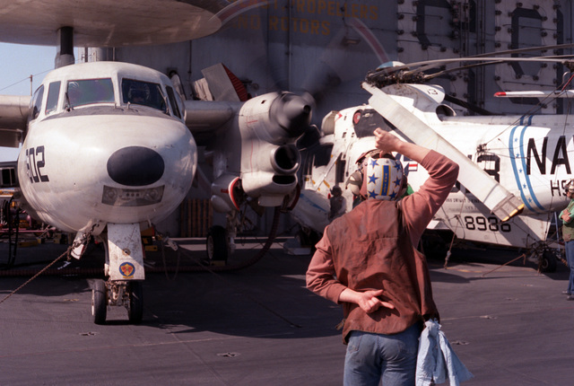 A flight deck crew member signals to the pilot of an Airborne Early Warning Squadron 121 (VAW-121) E-2C Hawkeye aircraft on the flight deck of the nuclear-powered aircraft carrier USS DWIGHT D. EISENHOWER (CVN-69)
