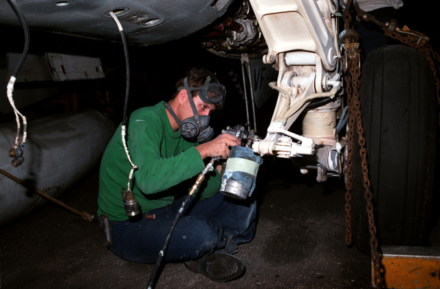A maintenance crew member paints the wheel strut of an F-14A Tomcat aircraft aboard the nuclear-powered aircraft carrier USS DWIGHT D. EISENHOWER (CVN 69)