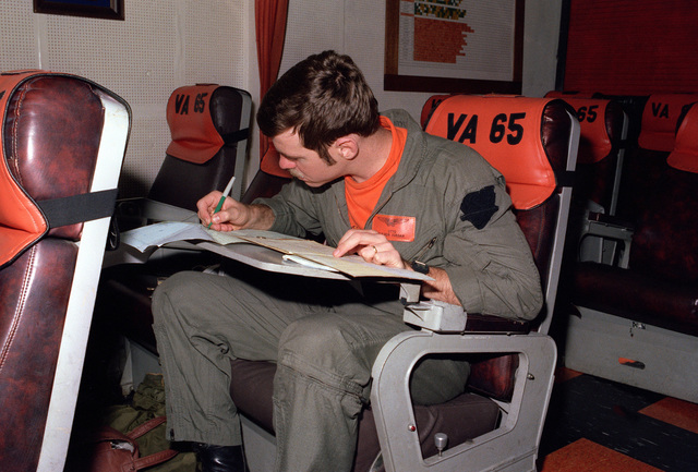 A member of Attack Squadron 65 (VA-65) takes notes during a preflight briefing in the squadron ready room aboard the nuclear-powered aircraft carrier USS DWIGHT D. EISENHOWER (CVN-69)