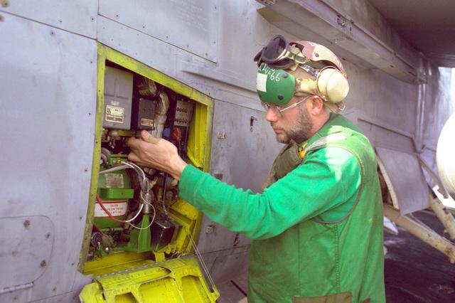 A member of Attack Squadron 66 (VA-66) makes an adjustment on an A-7E Corsair II aircraft on the flight deck of the nuclear-powered aircraft carrier USS DWIGHT D. EISENHOWER (CVN-69)