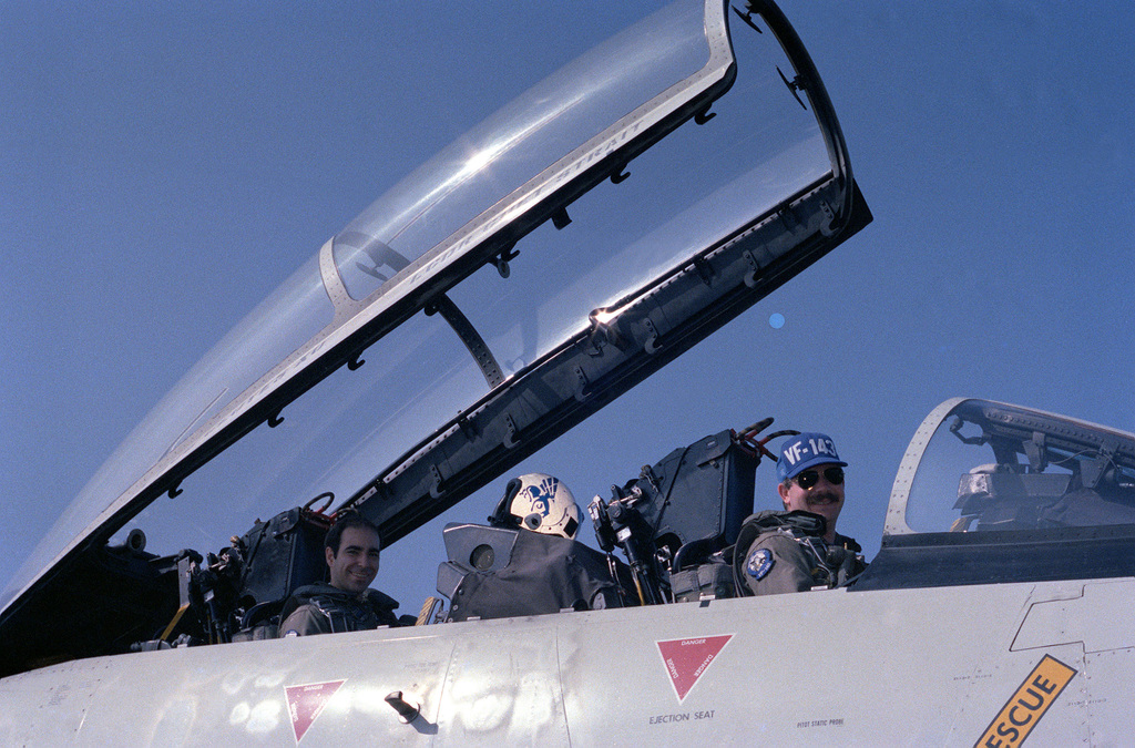 A pilot and radar intercept officer from Fighter Squadron 143 (VF-143) sit in the cockpit of their F-14A Tomcat aircraft on the flight deck of the nuclear-powered aircraft carrier USS DWIGHT D. EISENHOWER (CVN 69)