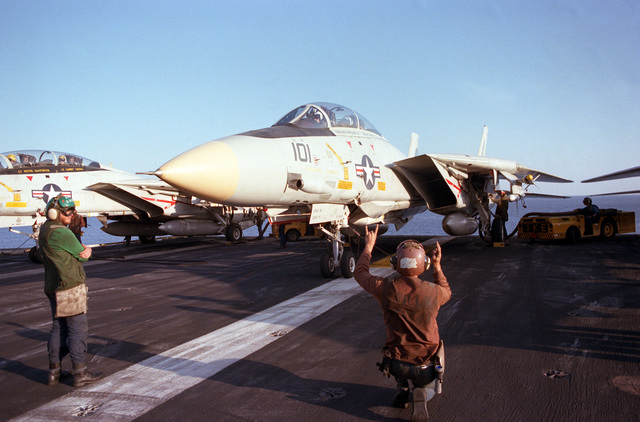 A plane captain signals to the pilot of a Fighter Squadron 143 (VF-143) F-14A Tomcat aircraft on the flight deck of the nuclear-powered aircraft carrier USS DWIGHT D. EISENHOWER (CVN 69). An MD-3A tow tractor is beneath the aircraft's wing at right