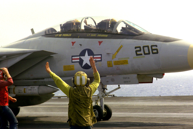 A plane director signals to the pilot of a Fighter Squadron 142 (VF-142) F-14A Tomcat aircraft on the flight deck of the nuclear-powered aircraft carrier USS DWIGHT D. EISENHOWER (CVN-69)