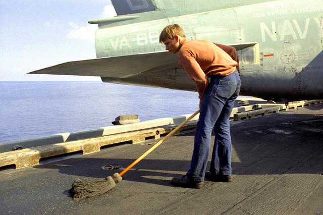A sailor swabs the deck of the nuclear-powered aircraft carrier USS DWIGHT D. EISENHOWER (CVN-69)