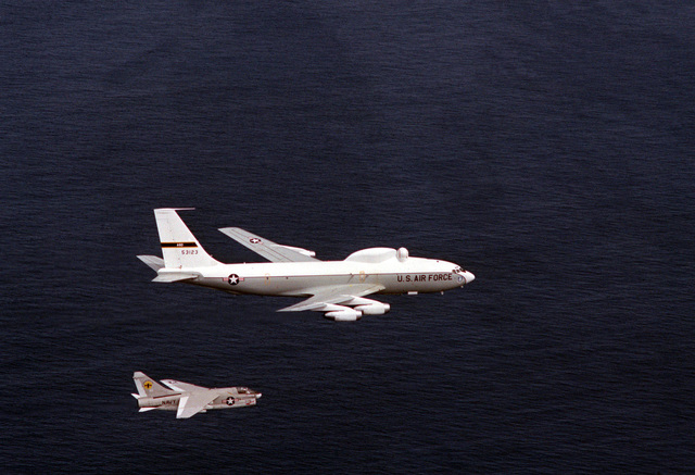 An air-to-air right side view of a US Air Force NKC-135A Stratotanker Airborne Laser Laboratory (ALL) aircraft and an A-7 Corsair II chase aircraft over the Pacific Missile Test Center range. The plane will be used to test targets