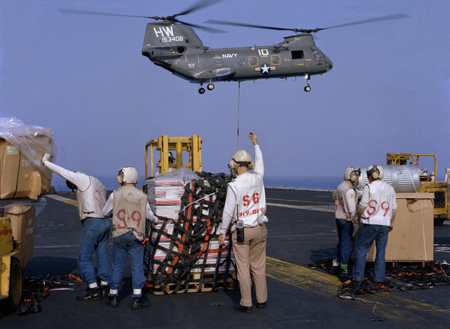 An aviation stores (S-6) divisional officer from the Supply Department aboard the nuclear-powered aircraft carrier USS DWIGHT D. EISENHOWER (CVN-69) signals to a forklift driver as a CH-46 Sea Knight helicopter of Helicopter Combat Support Squadron 6 (HC-6) hovers overhead during underway replenishment